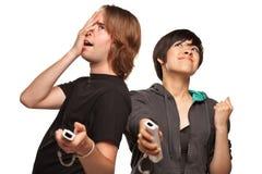 Couples de métis jouant des distants de jeu vidéo sur le blanc Photo libre de droits