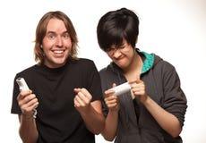 Couples de métis jouant des distants de jeu vidéo sur le blanc Photographie stock
