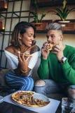 Couples de métis mangeant de la pizza en café moderne Image libre de droits