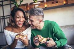 Couples de métis mangeant de la pizza en café moderne Photographie stock libre de droits