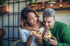 Couples de métis mangeant de la pizza en café moderne Images stock