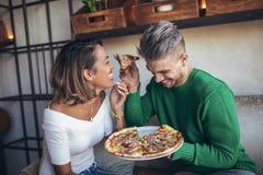 Couples de métis mangeant de la pizza en café moderne Images libres de droits