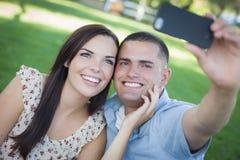 Couples de métis prenant l'autoportrait en parc Images libres de droits