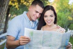 Couples de métis regardant au-dessus de la carte dehors ensemble Images stock