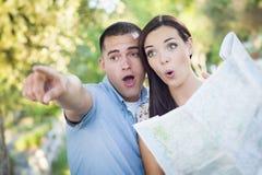 Couples de métis regardant au-dessus de la carte dehors ensemble Photos libres de droits