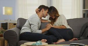 Couples de métis se reposant sur le divan avec des têtes ensemble Photos libres de droits