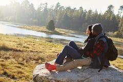 Couples de métis sur une roche dans la campagne admirant la vue Photos stock