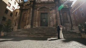 Couples de mariage à Rome embrassant près de l'église de San Nicola da Tolentino Belle jeune mariée et de marié ebraces élégants  banque de vidéos