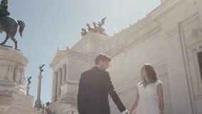 Couples de mariage à Rome posant devant le della Patria d'Altare à Rome, Italie Le marié élégant marche autour de la belle jeune  banque de vidéos