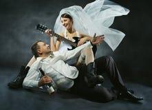 Couples de mariage célébrant, chantant, buvant et jouant la guitare Images stock
