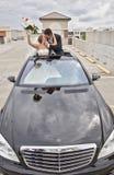 Couples de mariage dans le toit ouvrant de limousine photographie stock