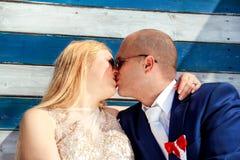 Couples de mariage embrassant près de la maison blanche bleue de mur Photo stock