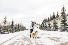 Couples de mariage et un chien mignon dans l'horaire d'hiver image libre de droits