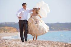 Couples de mariage fonctionnant sur la plage Images libres de droits