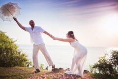Couples de mariage juste mariés avec le parapluie Image stock