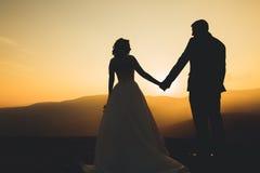 Couples de mariage posant sur le coucher du soleil au jour du mariage Mariée et marié dans l'amour Image libre de droits