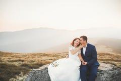Couples de mariage posant sur le coucher du soleil au jour du mariage Mariée et marié dans l'amour Photo stock