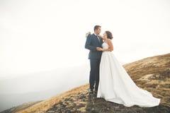 Couples de mariage posant sur le coucher du soleil au jour du mariage Mariée et marié dans l'amour Photographie stock