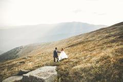 Couples de mariage posant sur le coucher du soleil au jour du mariage Mariée et marié dans l'amour Image stock