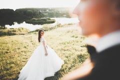 Couples de mariage posant sur le coucher du soleil au jour du mariage Mariée et marié dans l'amour Images libres de droits