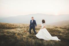 Couples de mariage posant sur le coucher du soleil au jour du mariage Mariée et marié dans l'amour Photo libre de droits