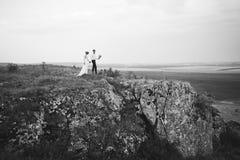 Couples de mariage regardant en colline de montagne sur le coucher du soleil Photo stock