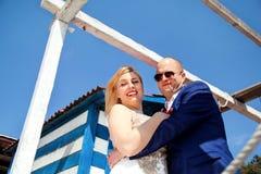 Couples de mariage restant près de la maison blanche bleue Photos stock
