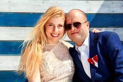 Couples de mariage se reposant près de la maison blanche bleue de mur Images libres de droits