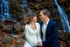 Couples de mariage se reposant sur la pierre Fond de cascade Lune de miel en montagnes d'automne Photographie stock libre de droits