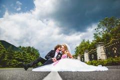 Couples de mariage se reposant sur la terre Images stock