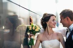 Couples de mariage sur des bâtiments de miroir de backround Image stock