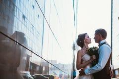 Couples de mariage sur des bâtiments de miroir de backround Photographie stock