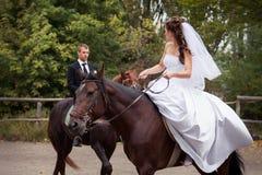 Couples de mariage sur des chevaux Photo stock