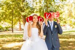 Couples de mariage tenant des mains dans l'amour de mot Images stock