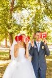 Couples de mariage tenant des mains dans l'amour de mot Photo libre de droits