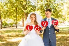 Couples de mariage tenant des mains dans l'amour de mot Photos libres de droits