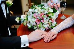 Couples de mariage tenant des mains sur le bouquet Marié et jeune mariée dans une PA Photographie stock libre de droits