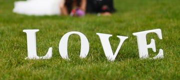 Couples de mariage unfocused et mot d'amour sur l'herbe Images stock