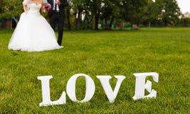 Couples de mariage unfocused et mot d'amour sur l'herbe Photographie stock