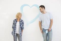 couples de Mi-adulte regardant l'un l'autre avec le coeur peint sur le mur Photo stock