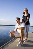 couples de Mi-adulte sur le dock par l'eau appréciant la boisson Photo stock