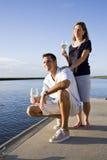 couples de Mi-adulte sur le dock par l'eau appréciant la boisson Photographie stock
