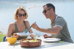 Couples de Moyen Âge en vacances mangeant dehors Images stock