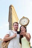 Couples de New York prenant le fer à repasser de touristes NYC de selfie Image stock