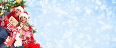 Couples de Noël heureux au-dessus de fond neigeux. Photographie stock libre de droits