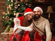 Couples de Noël heureux dans des décorations de nouvelle année à la maison Photos stock