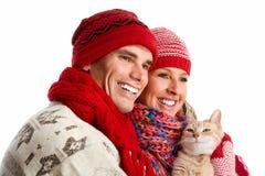 Couples de Noël heureux dans l'habillement d'hiver. Photographie stock libre de droits
