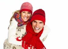 Couples de Noël heureux dans l'habillement d'hiver. Images stock