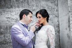 Couples de nouveaux mariés d'amusement, jeunes mariés posant près du vieux mur Images libres de droits