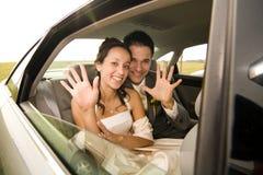 Couples de nouveaux mariés dans la limousine Photo stock
